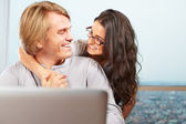 Happy couple in front of laptop — Stock Photo