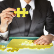 Royalty-Free Stock Photo: Businessman trying to finish the puzzle