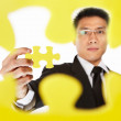 Businessman holding the last piece of puzzle — Stock Photo