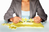 Businesswoman trying to solve the puzzle — Stock Photo