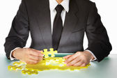 Businessman trying to finish the puzzle — Stock Photo