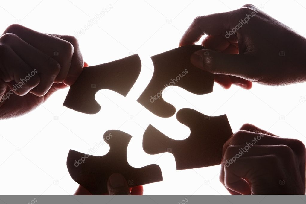 Hands try to solve the uncommon shape puzzle, taken in silhouette against bright white background — Stock Photo #10845521