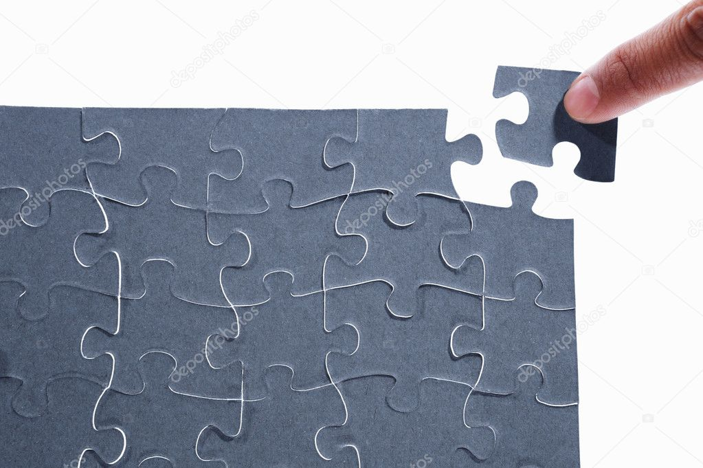 Finger putting the last piece of puzzle — Stockfoto #10846414