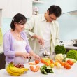 Asian couple busy in kitchen — Stock Photo
