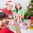 Little girl taking picture of her parent on Christmas — Stock Photo