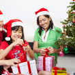 Little girl opening Christmas present with parents — Stock Photo