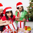Little girl opening Christmas present with parents — Stock Photo #10910153