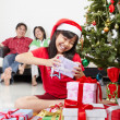 Stock Photo: Little girl busy with her Christmas present