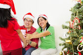 Girl giving Christmas present to her parents — Stock Photo