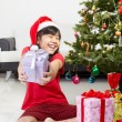 Little girl pointing Christmas present - Stock Photo