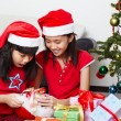 Kids busy opening Christmas present — Stock Photo #10992847