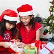 Stock Photo: Kids busy opening Christmas present