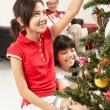 Asian girl decorating Christmas tree — Stock Photo