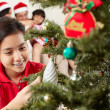 Asian girl decorating Christmas tree — Stock Photo #10995671