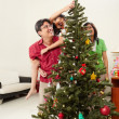 Asian family decorating Christmas tree — Stock Photo