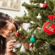 Asian little girl and Christmas tree - Stock Photo