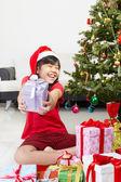 Malá holčička ukazující vánoční dárek — Stock fotografie