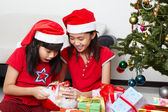 Kids busy opening Christmas present — Stock Photo
