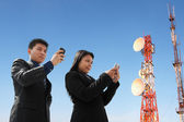 Asian business texting and antenna — Stock Photo