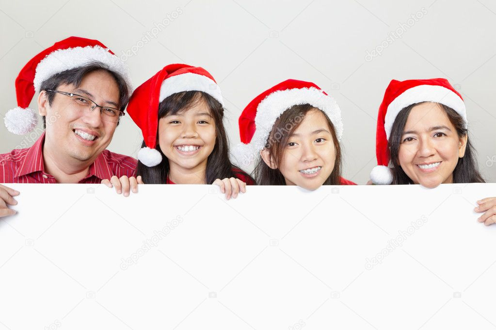 Asian family in Christmas outfit, pose in front of blank paper — Stock Photo #10992089
