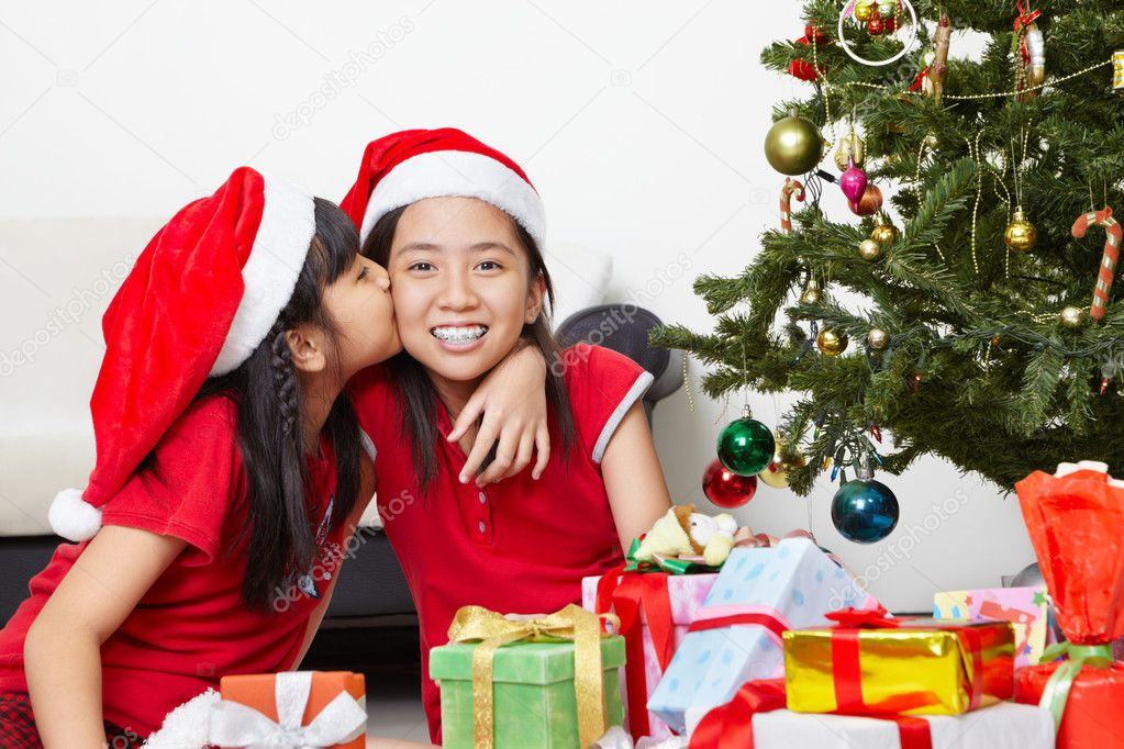 Tw little female siblings showing their love in Christmas season  Stock Photo #10992805