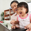 Mother and daughter playing laptop together — Stock Photo