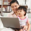 Stock Photo: Mother and daughter playing laptop together