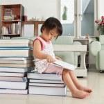 Litlle girl reading lot of books — Stock Photo