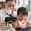 Stock Photo: Mother and daughter busy on their own