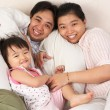 Chinese family having fun on bed — Stock Photo #11016522