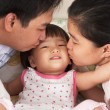 Parents kissing daughter — 图库照片