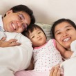 Chinese family having fun on bed — Stock Photo