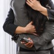 Business couple hug and kissing yet the woman still using cell p — Stock Photo