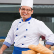 Chef or baker posing in front of the pastries — Stock Photo