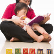 Stock Photo: Mother and her little girl reading book