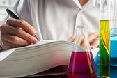 Scientist looking for data in journal — Stock Photo
