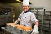 Baker holding fresh bread from oven — Stock Photo