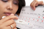 Sad woman with negative pregnancy test and calendar — Stock Photo