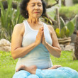 Asian senior woman meditating for yoga outside — Stock Photo