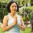 Asian senior woman meditating for yoga outside — Stockfoto