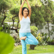 Senior woman doing yoga at park — Stockfoto