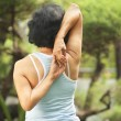 Senior woman doing yoga at park — Stock Photo #11037027