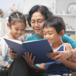 Grandma and grandchildren reading book together - Stock Photo