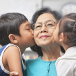 Grandmother being kissed by grandchildren at home - Stock Photo