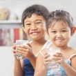 Two little girl and boy each holding glass of milk — Stock Photo #11039145