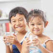 Two little girl and boy each holding glass of milk — Stock Photo