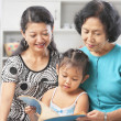 Little girl accompanied by mother and grandma reading book — Stockfoto
