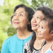 Three Asian female generations looking away — Stock Photo