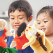 Sibling playing hand puppet — Stock fotografie