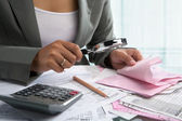 Businesswoman checking bills using magnifying glass — Stock Photo